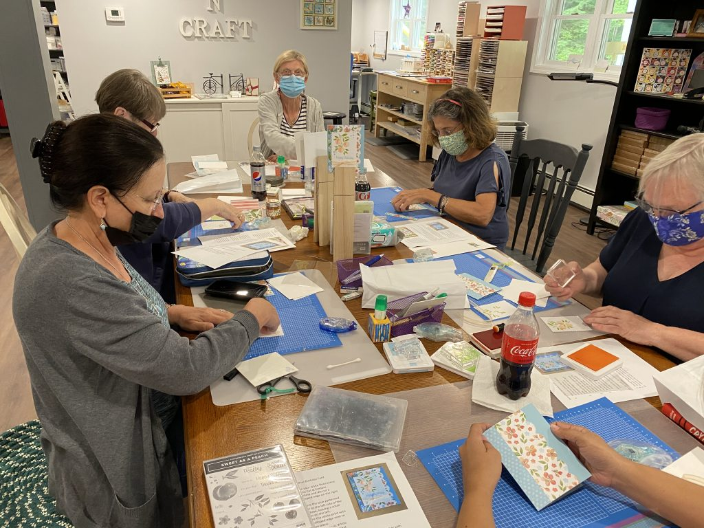 Photo of 6 people stamping and card making around a large table.
