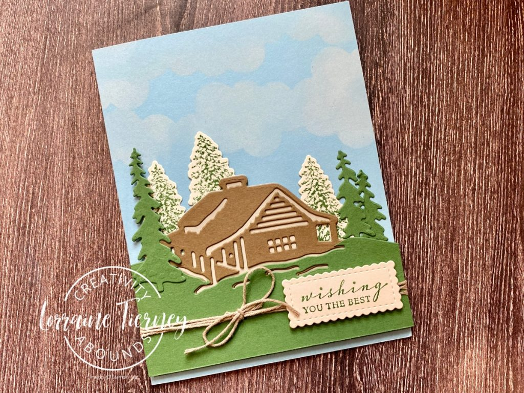 Photo of the Peaceful Cabin with clouds and trees behind a classic log cabin made with Stampin' Up! Peaceful Cabin bundle