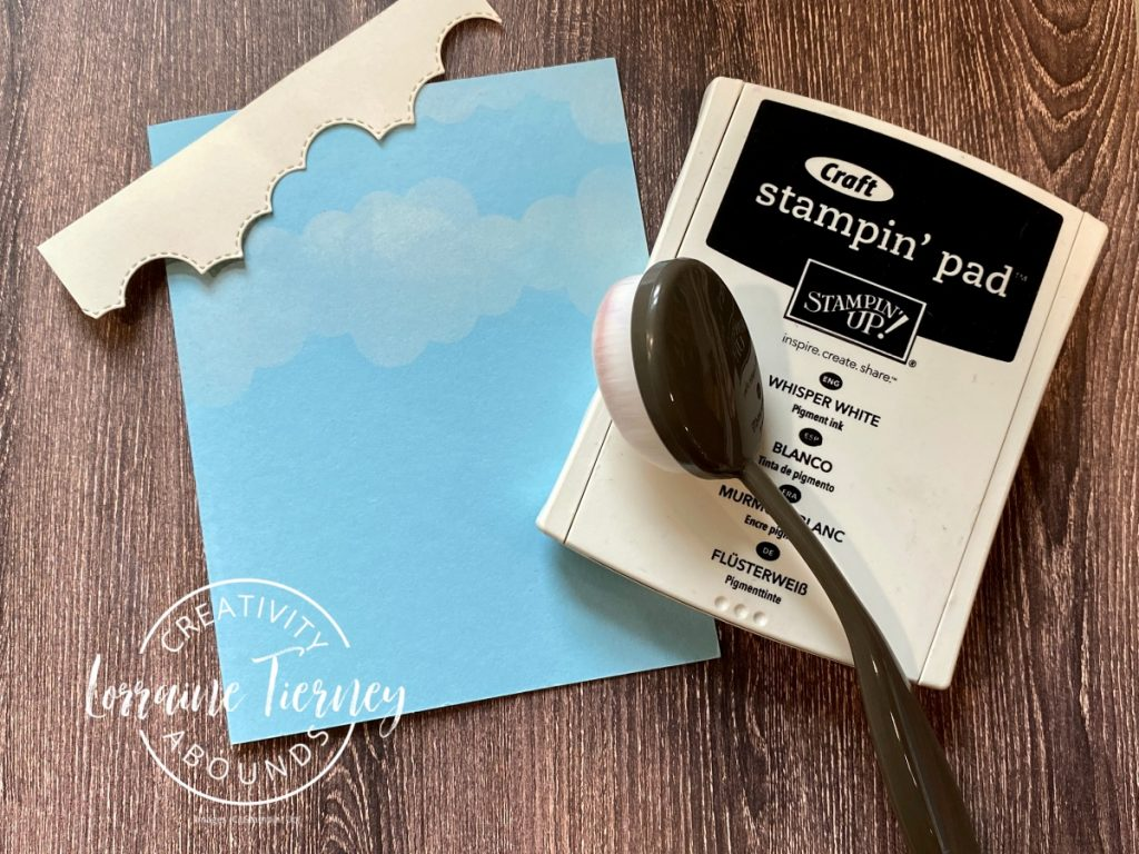 Close up photo of how to make the clouds for the Peaceful Cabin card using Blender brushes and white craft ink.
