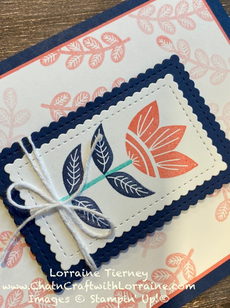 Close up photo of the Calypso Coral flower with Night of Navy leaves that is on the front of the featured card.